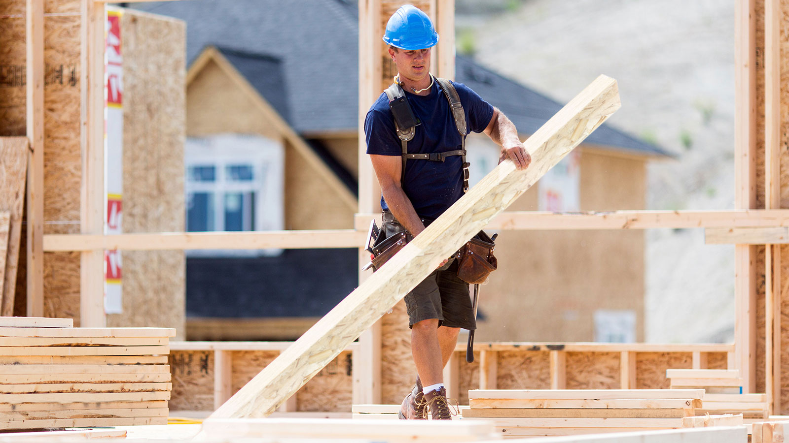 Worker carrying Tolko engineered wood product at construction site