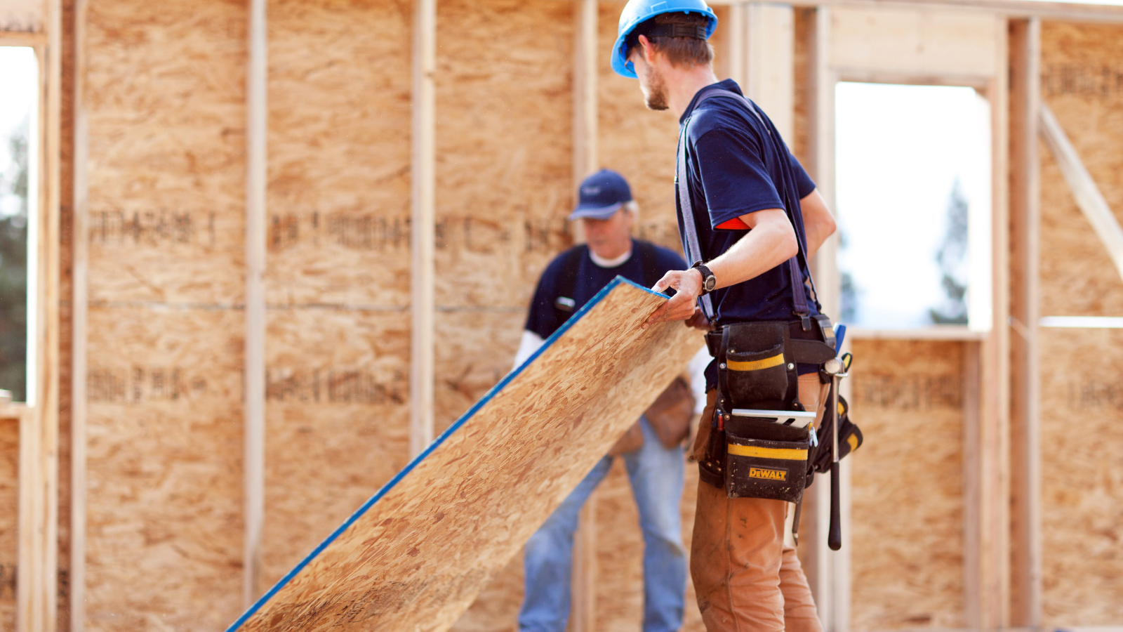 Worker holding OSB subfloor at residential construction site