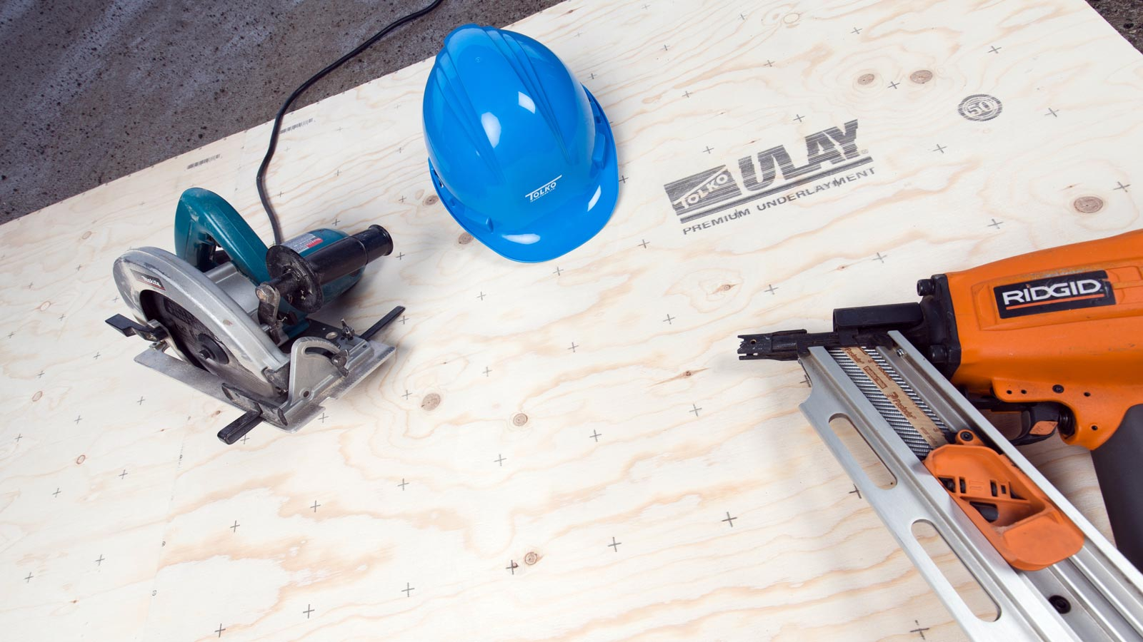 Tolko U-Lay product with skillsaw, hardhat and nail gun